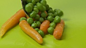 Carrots and peas with butter curls on green background