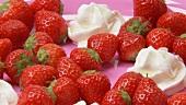 Frische Erdbeeren mit Sahnetupfen auf rosa Teller