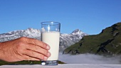 A glass of milk, mountains in background