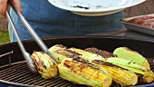 Taking grilled corn on the cob off a barbecue