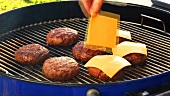 Putting cheese on burgers on a barbecue (for cheeseburgers)