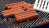 Würstchen auf den Grill legen (für Hot Dog)