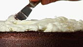 Spreading cream on a chocolate cake