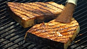 Brushing swordfish steaks on barbecue with marinade