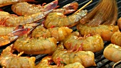 Brushing prawn skewers on a barbecue with barbecue marinade