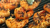Turning prawn skewers on a barbecue