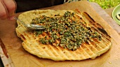 Spreading pesto on grilled flatbread