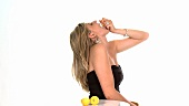 Blond woman squeezing lemon juice into her mouth