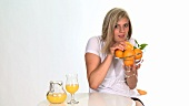 Blond woman holding a glass bowl of oranges