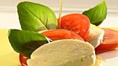 Olivenöl über die Tomaten- und Mozarellascheiben gießen