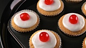 Cupcakes with cocktail cherries in muffin tin