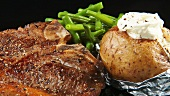 Fried T-bone steak with green beans and baked potato