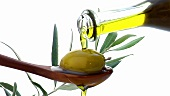 Pouring olive oil over a green olive