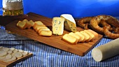 Romadur, Gorgonzola, obatzda, beer & pretzels on wooden board
