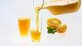 Pouring orange juice, orange wedges