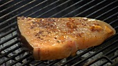 Putting marinated swordfish on barbecue