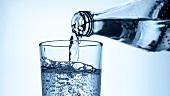 Ein Glas Mineralwasser einschenken