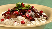 Beef with rice, pomegranate seeds and sesame seeds