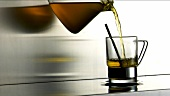 Grünen Tee in ein Glas gießen