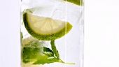 A glass of mineral water with mint leaves and slices of lime