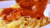 Serving ribbon pasta with tomato sauce and prawns