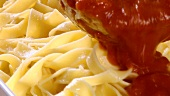 Serving ribbon pasta with tomato sauce