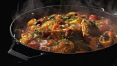 Braised chicken and vegetables in a frying pan