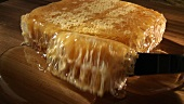 Cutting a piece of honeycomb with honey