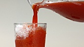 Pouring tomato juice into a glass filled with ice