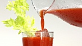 Pouring tomato juice into a glass with celery and ice
