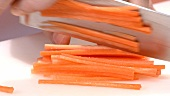 Cutting a carrot into sticks (close-up)