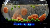 Peas and carrot slices being dropped into hot water