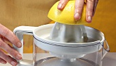 Squeezing grapefruit with an electric citrus squeezer