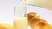 Pouring grapefruit juice out of a jug into a chilled glass