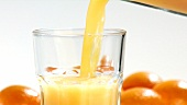 Pouring orange juice into a glass (close-up)