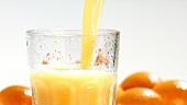 Pouring orange into a chilled glass (close-up)
