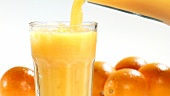Pouring orange juice into a glass of crushed ice