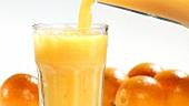 Orangensaft in ein Glas mit Crushed Ice gießen