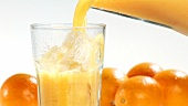 Pouring orange juice into a glass of ice cubes