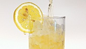 Pouring apple juice into a glass of crushed ice with a slice of lemon