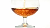 Pouring a glass of cognac (close-up)