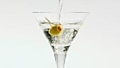 Martini in ein Glas mit Olive eingiessen