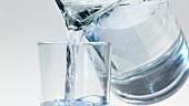 Mineralwasser aus der Kanne in ein Glas gießen