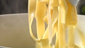 Putting cooked ribbon pasta into a bowl