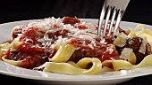 Ribbon pasta with meatballs, tomato sauce and Parmesan