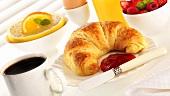 Frühstück mit Croissant, Marmelade, Kaffee und Obst