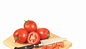 Whole and chopped tomatoes with knife on wooden board