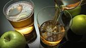 Apfelsaft in Gläser gießen