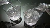 Pouring water into two glasses containing ice cubes