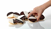 A pile of black-and-white cookies and a hand taking one